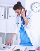 Portrait of young woman doctor in white coat at computer using phone