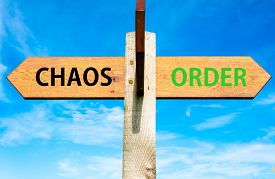picture of opposites  - Wooden signpost with two opposite arrows over clear blue sky Chaos versus Order messages - JPG
