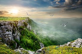 stock photo of plateau  - Birds over plateau at the cloudy sunset - JPG