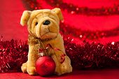 stock photo of christmas dog  - Toy dog with christmas ornaments over red - JPG