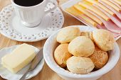stock photo of brazilian food  - Brazilian snack pao de queijo (cheese bread) on white plate with cheese ham butter cup of coffee on wooden table. Selective focus ** Note: Shallow depth of field - JPG
