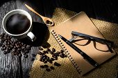 stock photo of sackcloth  - Cup of coffee and coffee beans on sackcloth with light and shadow on wooden table - JPG
