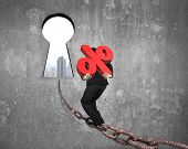 foto of keyholes  - Man carrying 3D red percentage sign walking on old iron chain toward keyhole door with urban scene view and gray concrete wall background - JPG