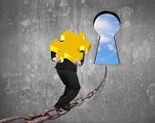 picture of keyholes  - Man carrying golden jigsaw puzzle walking on old iron chain toward keyhole door with sky clouds view and gray concrete wall background - JPG