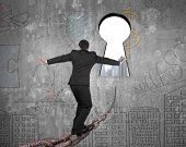 stock photo of keyholes  - Man balancing on old iron chain toward keyhole with cityscape view and business concept doodles wall background - JPG