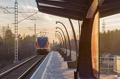 stock photo of electric station  - Sunset view on electric train departure from small railroad station - JPG