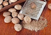 foto of grating  - Ground nutmeg grated on wooden table background - JPG