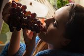 foto of refrigerator  - young beauty woman eating grapes near refrigerator - JPG