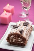 image of yule  - Yule log cake decorated with chocolate leaves on a Christmas table - JPG