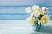 foto of vase flowers  - Bright white daffodils and tulips flowers in blue vase on turquoise painted wooden planks against blue wall. Selective focus. Place for text.
