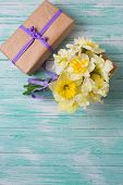 stock photo of gift wrapped  - Bunch of fresh spring yellow daffodils flowers amd wrapped gift box on turquoise painted wooden planks - JPG