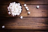 picture of sugar cube  - White sugar cubes in bowl on dark wooden background - JPG