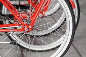 image of fragmentation  - Parked red street bicycles for rent rear wheels fragment selective focus with shallow DOF - JPG