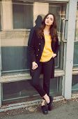 image of blouse  - Young woman portrait with long brown hair dressed in black trenchcoat and yellow blouse - JPG