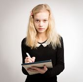 pic of hair bow  - Beautiful young blond teenage girl writing down notes on a notepad wearing a black top and a bow in her hair isolated against a white background - JPG