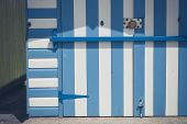 stock photo of beach hut  - A colorful beach hut painted with blue and white stripes - JPG