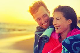 picture of bathing  - Bathing romantic couple with towel on beach sunset - JPG