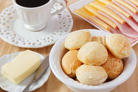 picture of brazilian food  - Brazilian snack pao de queijo (cheese bread) on white plate with cheese ham butter cup of coffee on wooden table. Selective focus