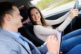 picture of driving school  - Driving instructor and woman student in examination car - JPG
