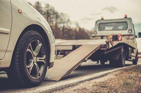 pic of trucks  - Loading broken car on a tow truck on a roadside  - JPG