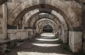stock photo of empty tomb  - Empty corridor with arcs and columns - JPG