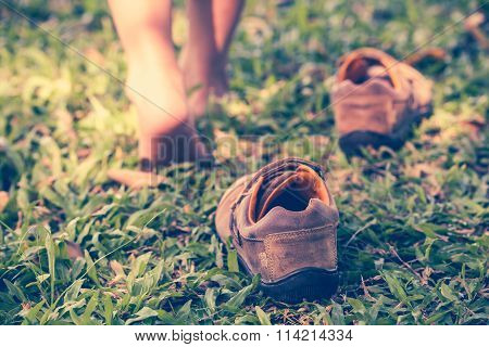 Child Take Off Shoes. Child\'s Foot Learns To Walk On Grass