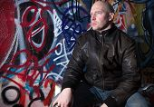 stock photo of deprivation  - man with attitude in front of graffiti wall in urban area - JPG