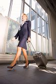 businesswoman with trolley in the airport waiting for departure