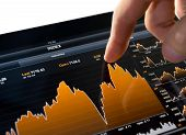 image of stock market data  - Touching stock market graph on a touch screen device - JPG