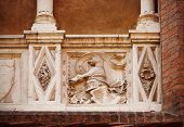 Old balcony with colums and emblem (Bologna, Italy)
