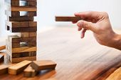 Business Man Placing Wooden Block On A Tower Concept Of Risk Control Planning Risk And Strategy. poster