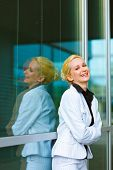 Laughing modern business woman with crossed arms on chest at office building