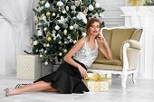 Christmas, winter holidays concept. Beautiful charming woman in evening dress with a gift box. Luxur poster