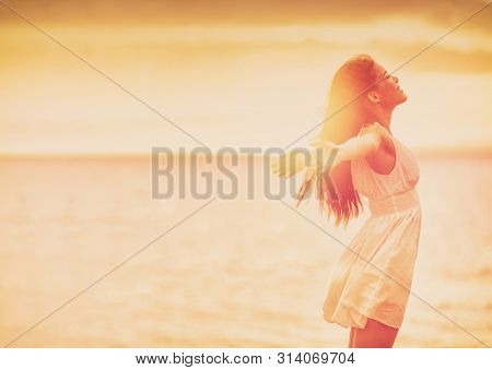 poster of Wellness woman feeling free with open arms in freedom side profile silhouette on ocean beach backgro