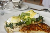 stock photo of benediction  - Eggs Florentine benedict with hash brown potatoes on a formal breakfast table