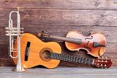 Musical Instruments Of Vintage Style. Trumpet, Acoustic Guitar And Violin On Wooden Background. Clas poster