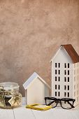 Houses Models On White Wooden Table With Moneybox, Calculator And Glasses Near Brown Textured Wall,  poster