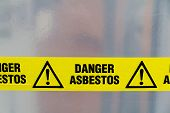 stock photo of asbestos  - Danger Asbestos yellow warning tape close up - JPG