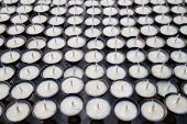 White Candles Background.buddhism Candles In A Row.buddhism Praying Ceremony poster