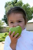 Little Girl Eating A Green Apple