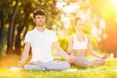 Couples Yoga, man and woman doing yoga exercises, meditate in sunny the park. Yoga outdoor. Concept  poster