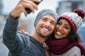 Happy multiethnic couple in the city taking photo in a winter day. Smiling man and african girl taki poster