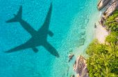 Travel concept with airplane shadow and tropical beach. Tropical paradise and beach holiday conceptu poster
