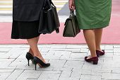 High-heeled Shoes, Female Fashion. Two Women With Purses Stand On The Street In High Heels Before Th poster
