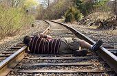 picture of train track  - A man laying on the railroad tracks - JPG
