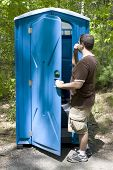 picture of porta-potties  - A young man investigating a blue porta potty located on the hiking trail - JPG