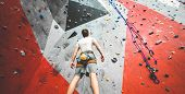Sportsman Climber Is Looking On Steep Rock, Climbing On Artificial Wall Indoors. Extreme Sports And  poster