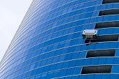 stock photo of cleaning service  - Two window cleaners in a gondola cleaning the windows of a corporate office skyscraper - JPG