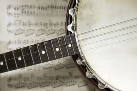 stock photo of musical instrument string  - grunge banjo with a music score background - JPG