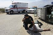 stock photo of accident victim  - Police officer checking pulse of car crash victim - JPG